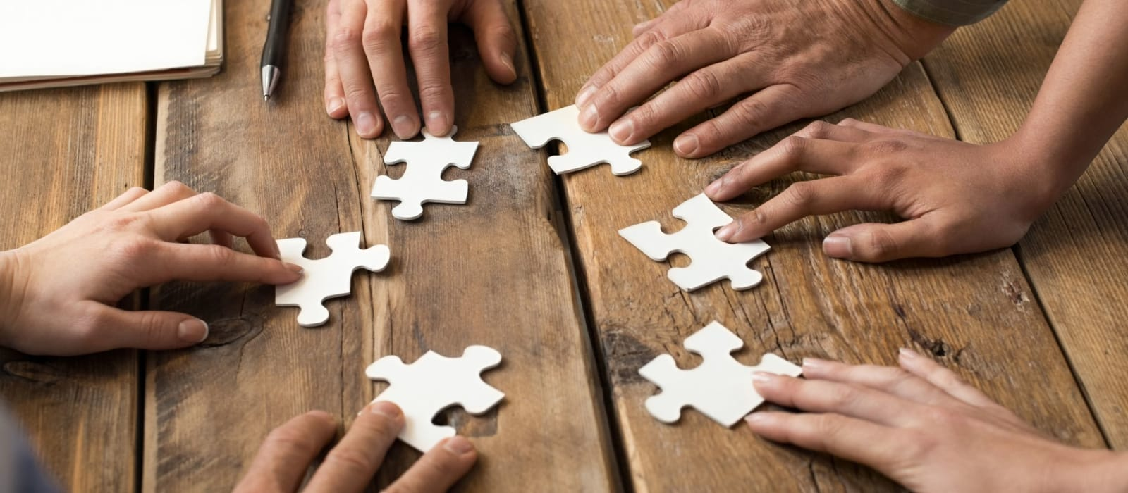 Hands putting together jigsaw