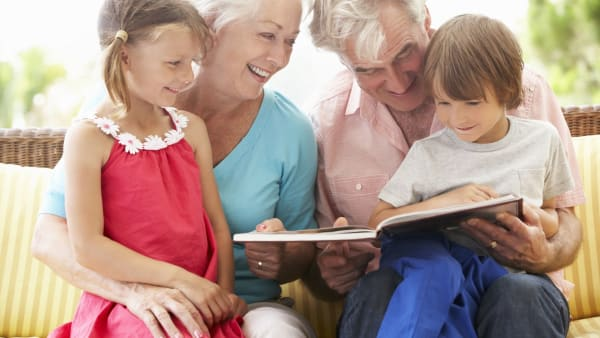 Granparents reading story with grandchildren